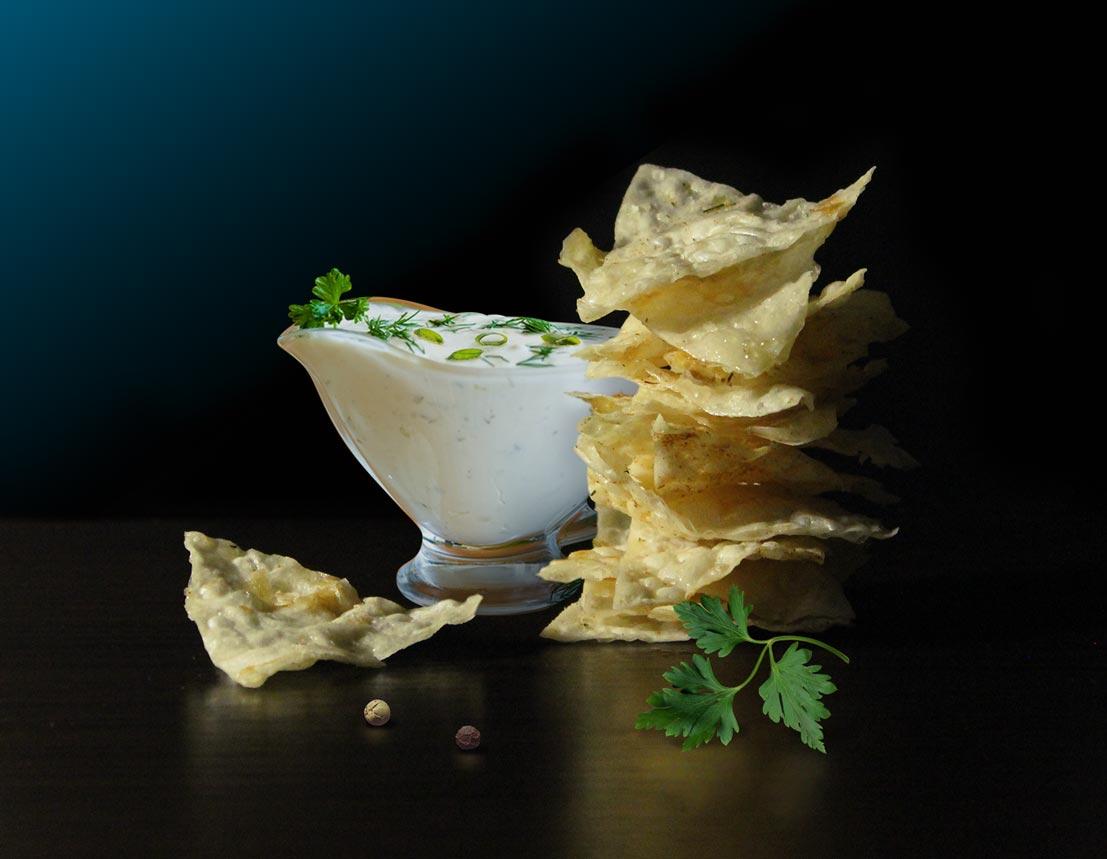 Постановочная фото съемка продуктов чипсы, сметана и лук